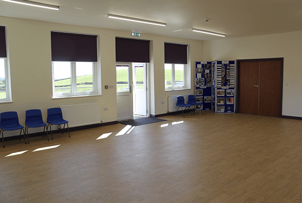 Inside view of the main room of the Community Centre looking out across the fields
